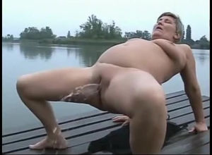 Grandma pissing near a lake